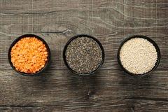 Diversos tipos de granos sanos en cuencos en fondo de madera fotos de archivo