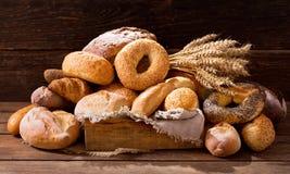 Diversos tipos de pan cocido fresco con los oídos del trigo Imagenes de archivo