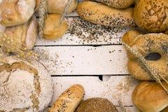 Diversos tipos de pan en el tablero de madera blanco Imágenes de archivo libres de regalías