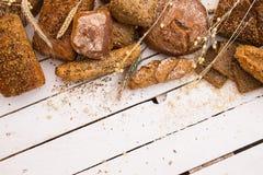 Diversos tipos de pan en el tablero de madera blanco Imagenes de archivo