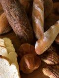 Diversos tipos de pan en la tajadera de madera Foto de archivo