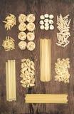 Diversos tipos de pastas crudas italianas en el fondo de madera rústico de la tabla, visión superior Imagen de archivo