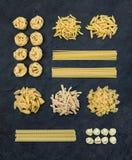 Diversos tipos de pastas crudas italianas en pizarra negra empiedran el fondo, visión superior Imagen de archivo libre de regalías