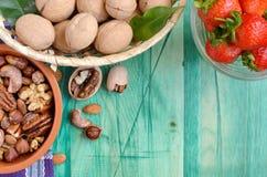 Diversos tipos de porcas em uma bacia marrom de morangos em um alimento saudável de vidro transparente em um fundo verde fotos de stock
