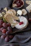 Diversos tipos de queso con la uva en el tablero de madera imagenes de archivo