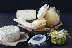 Diversos tipos de queso en un fondo negro Disco del queso imagenes de archivo