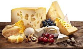 Diversos tipos de queso sobre la tabla de madera vieja. Fotos de archivo libres de regalías