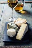 Diversos tipos de queso y de vino blanco Imagen de archivo