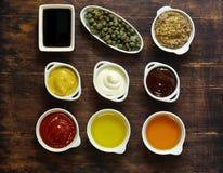 Diversos tipos de salsas y de aceites en cuencos Foto de archivo