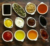 Diversos tipos de salsas y de aceites en cuencos Imagen de archivo