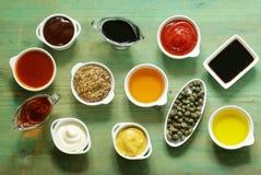 Diversos tipos de salsas y de aceites en cuencos Fotografía de archivo