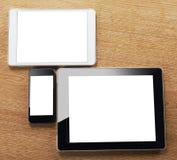 Diversos tipos de tablilla digital y de teléfono elegante en una mesa imagen de archivo