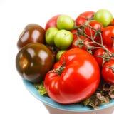 Diversos tipos de tomates en un cuenco en la tabla Foto de archivo