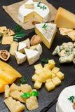 Diversos tipos del queso - brie, camembert, el Roquefort y Cheddar en el hormigón Fotografía de archivo