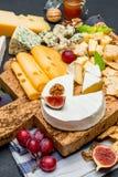 Diversos tipos del queso - brie, camembert, el Roquefort y Cheddar en el tablero de madera Imagen de archivo