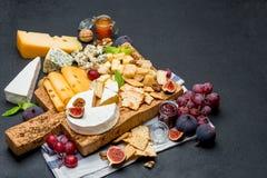 Diversos tipos del queso - brie, camembert, el Roquefort y Cheddar en el tablero de madera Fotos de archivo
