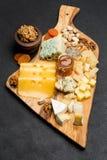 Diversos tipos del queso - brie, camembert, el Roquefort y Cheddar en el tablero de madera Fotografía de archivo libre de regalías