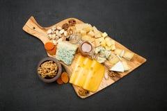 Diversos tipos del queso - brie, camembert, el Roquefort y Cheddar en el tablero de madera Foto de archivo