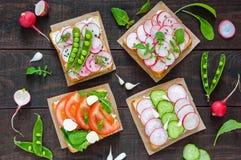 Diversos tipos dos sanduíches com vegetais: rabanete, tomates, pepino, rúcula no brinde friável Imagens de Stock