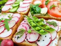 Diversos tipos dos sanduíches com vegetais: rabanete, tomates, pepino, rúcula no brinde friável Fotografia de Stock Royalty Free