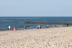 Diversos veraneantes andam ao longo da linha costeira Fotos de Stock