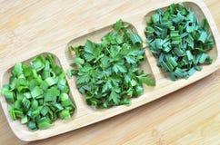 Diversos verdes cortados en trozos pequeños en el tablero de la cocina, en una placa de madera fotos de archivo