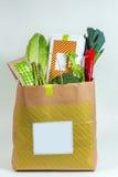 Diversos verdes frescos, verduras y caja blanca en bolsa de papel Foto de archivo