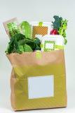 Diversos verdes frescos, verduras y caja blanca en bolsa de papel Imágenes de archivo libres de regalías