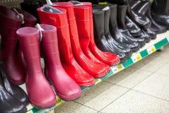 Diversos waterboots rojos y negros están en estantes de la tienda Imagen de archivo