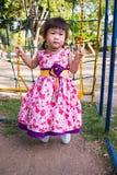 Divertimento adorável da menina no balanço no parque Luz solar no pla das crianças Fotografia de Stock Royalty Free