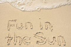 Divertimento al sole scritto in sabbia sulla spiaggia Fotografia Stock
