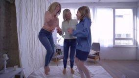 Divertimento alegre da família, da mãe e das filhas que salta na cama e que abraça então junto na câmera filme