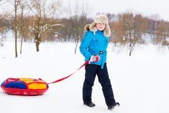 Divertimento ativo do inverno - passeio feliz da menina do monte da neve nos tubos imagem de stock