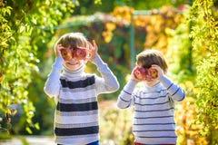 Divertimento da família durante o tempo de colheita em uma exploração agrícola Crianças que jogam no jardim do outono fotografia de stock royalty free