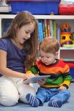 Divertimento da menina e do irmão usando um tablet pc digital Fotografia de Stock