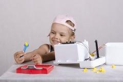 Divertimento da menina que guarda uma porca da chave, reparando o brinquedo Imagem de Stock Royalty Free