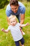 Divertimento de And Daughter Having do pai que joga o jogo fora Foto de Stock Royalty Free