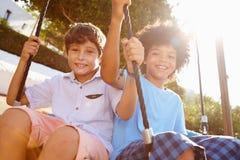 Divertimento de dois meninos das meninas no balanço no campo de jogos Imagens de Stock Royalty Free