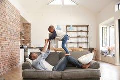 Divertimento de And Son Having do pai que joga em Sofa Together imagens de stock