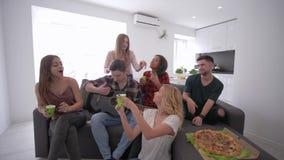 Divertimento degli amici che balla e che canta con la chitarra che si siede sul sofà con le tazze di plastica in loro mani in un