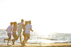 Divertimento degli amici sulla spiaggia nell'ambito di luce solare di tramonto immagini stock libere da diritti