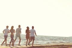 Divertimento degli amici sulla spiaggia nell'ambito di luce solare di tramonto fotografia stock