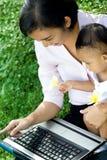 Divertimento del bambino e della madre con un computer portatile fotografia stock libera da diritti