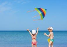 Divertimento del gioco dei fratelli germani dei bambini dell'aquilone della spiaggia Fotografia Stock Libera da Diritti