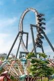 Divertimento del parco di divertimenti, montagne russe, capovolte, ciclo, giorno, cielo blu, annunciante Fotografie Stock