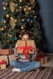 Divertimento dell'adolescente della ragazza che dà una occhiata dal contenitore di regalo che si siede vicino all'albero del nuov fotografia stock libera da diritti