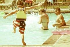 Divertimento della famiglia alla piscina locale immagini stock