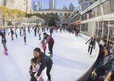 Divertimento della famiglia alla pista di pattinaggio di Bryant Park in New York Immagini Stock