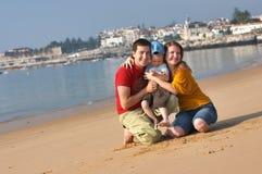 Divertimento della famiglia alla spiaggia sabbiosa Immagine Stock