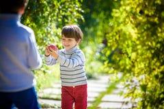 Divertimento della famiglia durante il tempo di raccolto su un'azienda agricola Bambini che giocano in autunno immagine stock libera da diritti
